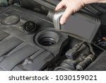 Small photo of Add up oil to car engine from bottle.