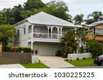 White queenslander home with tropical  greenery and tall trees on overcast day in Australia