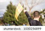 Small photo of Football soccer arbiter assistant observes the match and raises the flag with his hand. Blurred blue sky, nature, players background, close up view, details.