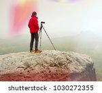 Small photo of Photographer think about picture on peak in the misty mountains. Photograph at daybreak above valley hidden in heavy mist. Landscape view of misty autumn mountain. Leak of light.