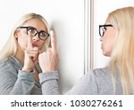 Small photo of A woman talks to her reflection in front of a mirror.