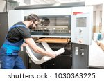 Small photo of Worker in unifrom getting printed sheets from the offset machine at the printing manufacturing
