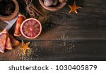 Small photo of Ingredients for making candied fruits. Fresh red orange fruit, spices and walnuts on rustic wooden table. Home cooking, baking and preserving concept. Food background. Flat lay, copy space for text
