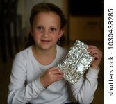 Small photo of Girl Found it! Afikoman is a half-piece of matzah which is broken of the Passover Seder.In many families the father takes the afikoman and hides it.The child that finds the afikoman receives gift.