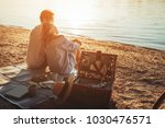 a young couple having a picnic... | Shutterstock . vector #1030476571