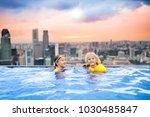 children swimming in roof top... | Shutterstock . vector #1030485847
