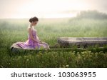 Romantic portrait of young woman in airy pink dress sitting in ruins at sunrise - stock photo