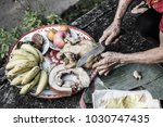 Small photo of Hand of old woman using a knife cut food, pox, chicken, fruits for pray and make offering. For luck In various events such as New Year, and a new home, ordained, and marriage.