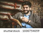 smiling young man reading book... | Shutterstock . vector #1030754059