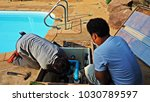 Technician fixing swimming pool water pump. Service and maintenance for swimming pool. - stock photo