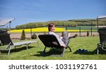 woman relaxing on a sun lounger ... | Shutterstock . vector #1031192761
