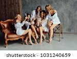 Small photo of Diverse group of female friends enjoying at a party and laughing. Group Of beautiful women having fun and Sitting on Sofa. Ladies in white clothes