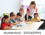 female teacher helping children ... | Shutterstock . vector #1031603941