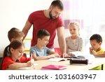male teacher helping children... | Shutterstock . vector #1031603947