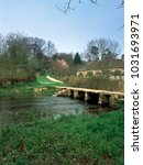 Small photo of The ancient clapper bridge over the River Leach at Eastleach in The Cotswolds, Gloucestershire, UK