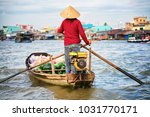 woman in a boat selling... | Shutterstock . vector #1031770171