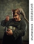 Small photo of Horned aggressive demon cooking a soup over grunge background