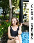Small photo of young female relax, enjoy weather in tropical country on background of apartment building on sunny day with sunshine. Concept of enjoying life, tratement for healthy body and relaxation