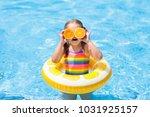 little girl in swimming pool... | Shutterstock . vector #1031925157