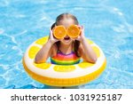 little girl in swimming pool... | Shutterstock . vector #1031925187