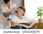 caring volunteer combing hair... | Shutterstock . vector #1032193075