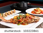 Freshly prepared Thai style whole fish red snapper dinner with sweet and sour shrimp and pan fried gyoza dumplings appetizer. - stock photo