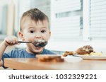 child in the kitchen eating... | Shutterstock . vector #1032329221