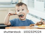 child in the kitchen eating... | Shutterstock . vector #1032329224