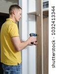 the man is installing a hook... | Shutterstock . vector #1032413344