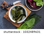Small photo of Wet soaked kombu seaweed leaves (nori, wakame, kelp) good to serve with fresh vegetables - broccoli, onion and spinach. Raw diet. Asian, japanese traditional food. Vegan, vegetarian healthy concept.