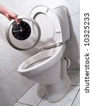 Small photo of Hand throwing clock per a toilet bowl. Flush time into a toilet, dally away