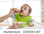 mum feeds baby boy from a spoon ... | Shutterstock . vector #1032531187