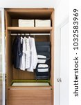 shirts hanging in wooden closet ... | Shutterstock . vector #1032583969