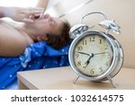 awaked man lying in the bed and ... | Shutterstock . vector #1032614575