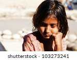 Stock photo poverty portrait of a poor little indian girl lost in deep thoughts 103273241