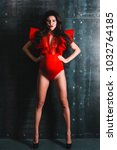 Small photo of Superwoman. Beautiful young pregnant woman in red bodysuit keeping arms akimbo while standing against concrete background