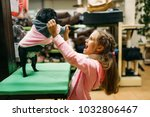 Stock photo little girl try on clothes for puppy in pet shop 1032806467