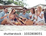 Small photo of Group of friends having great time together on the beach,eating pizza,play guitar and enjoy.