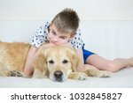 happy boy playing with golden... | Shutterstock . vector #1032845827