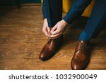 a man in a blue suit ties up... | Shutterstock . vector #1032900049