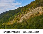 A colorful autumn landscape on a mountain slope. The rays of the sun through the yellow foliage of different trees. A picturesque rock under the blue sky with white clouds.