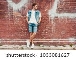 casual young man stands with... | Shutterstock . vector #1033081627