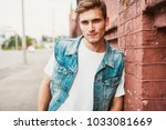 casual young man stands with... | Shutterstock . vector #1033081669