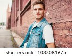 casual young man stands with...   Shutterstock . vector #1033081675