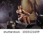 female using rowing machine in... | Shutterstock . vector #1033121659