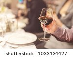 adult hand holding glass of red ... | Shutterstock . vector #1033134427