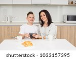 mother and son using digital... | Shutterstock . vector #1033157395