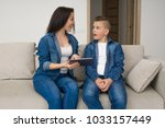 happy mother and son sitting on ... | Shutterstock . vector #1033157449