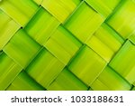 Small photo of basket making, zigzag weave of palm leaf, green foliage interlace texture background