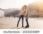 Small photo of Innermost thoughts. Full length of young romantic couple is standing outdoors. Elegant girl in sunglasses is telling her secrets to her boyfriend